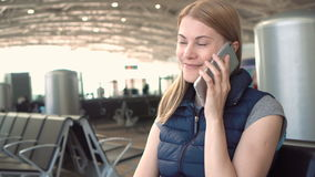 Beautiful attractive young woman using smartphone in airport. Talking to her friend. Smiling. No people around stock video footage