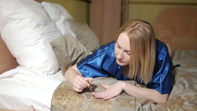 Beautiful attractive young women in bedroom paints nails.  stock footage