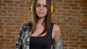 Beautiful attractive young women in glasses, headphones, posing in front of camera, turning away, female builder, brick. Beautiful attractive young women in stock video footage
