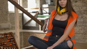Beautiful attractive young women in helmet and headphones taking wrench from tool box and twisting spanner, female