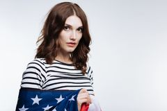 Beautiful auburn-haired woman posing wrapped in US flag Royalty Free Stock Photos