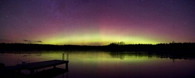 Beautiful Aurora in December. Beautiful Northern Lights panorama with reflection on a lake water surface. Usually the northerl lights are visible only with very Royalty Free Stock Images