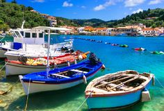 Beautiful authentic Greece - pictorial bay with fishing boats. Traditional fishing boats ,azure sea and colorful houses in Lakka beach,Paxos island,Greece Stock Photos