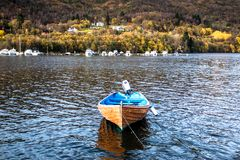 Autumn Landscape with A Wooden Blue Boat Resting at A Dock in A Fjord and Colorful Trees on Mountain royalty free stock image