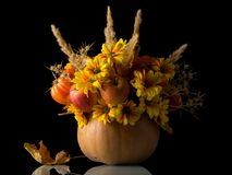 Beautiful autumn bouquet in pumpkin, made from flowers and apples, isolated on black royalty free stock images