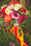 Beautiful autumn Bridal bouquet of different flowers on the grass, beautifully decorated with satin ribbons and jewelry. Wedding stock images