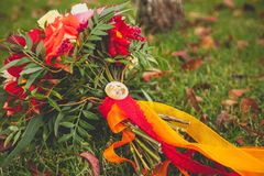 Beautiful autumn Bridal bouquet of different flowers on the grass, beautifully decorated with satin ribbons and jewelry. Wedding royalty free stock images