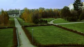 Autumn city park. Beautiful autumn city park, trees with bare branches and fallen leaves, green grass, people walk on park paths, family rest on weekend, parents stock video