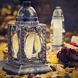 Beautiful autumn concept to the cemetery and Halloween. Candle in a lantern on the grave. Background for Halloween. Stock Image