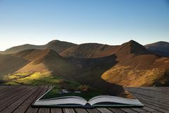 Beautiful Autumn Fall landscape image of sun beams lighting up small area of mountain side in Lake District coming out of pages of. Stunning landscape image of stock images