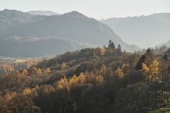 Beautiful Autumn Fall landscape image of the view from Catbells in the Lake District with vibrant Fall colors being hit by the