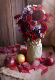 Beautiful autumn flower composition design. Beautiful autumn flower  composition design decoration in rustic vase with appes and red leaves. Rustic style and Royalty Free Stock Images