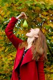 Beautiful autumn foliage on a nature woman decided to eat green pear royalty free stock images