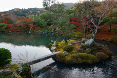 Beautiful autumn lake with a bridge to a small island and red maples growing on the banks Stock Image
