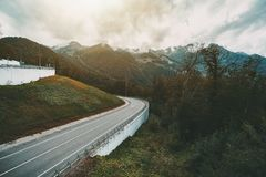 Bending road in autumn mountains. Beautiful autumn landscape with bending mountain highway bending after the hill, overcast sky, hills ridge in background Royalty Free Stock Photos