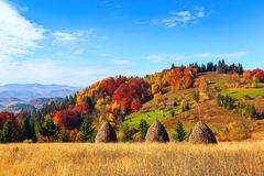 Beautiful autumn landscape with the green fair trees, orange coloured forest, high mountains and blue sky. Autumn village scene stock images