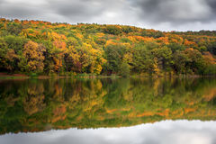 Beautiful autumn landscape. Green golden forest reflect on water lake Stock Image