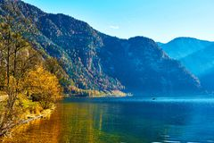 Beautiful autumn landscape of Hallstatt lake with boat and trees at sunny day in Austrian Alps, Salzkammergut region. Beautiful autumn landscape of Hallstatt royalty free stock photography