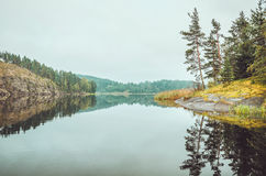 Beautiful autumn landscape with lake, pine trees, natural stone coast in the Republic of Karelia, Ladoga , northern Stock Photo