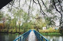 Long blue bridge. Beautiful autumn landscape on a long blue bridge across the river Royalty Free Stock Images