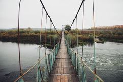 Long suspension bridge. Beautiful autumn landscape on a long suspension bridge across the river to the forest Stock Photography