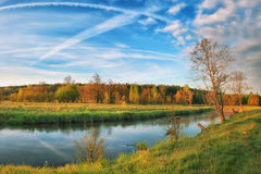 Beautiful autumn landscape of river in nature of bright day blue sky with white clouds Royalty Free Stock Photo