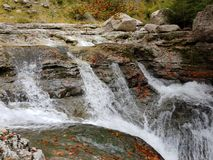 Beautiful autumn landscape with varied colours of browns, greens, oranges and yellows on the leaves of the trees next to the river. And a waterfall. Image stock photography