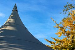 Beautiful autumn landscape with white event marquee tents roof against blue sky stock photography