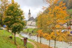 Beautiful autumn maple trees by the stream and a wooden bridge in front of a church with foggy mountains in the distant background stock photography