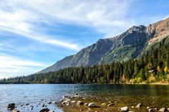 Beautiful autumn mountain landscape. With a lake and a forest at the foot of rocky mountains against the blue sky Stock Images
