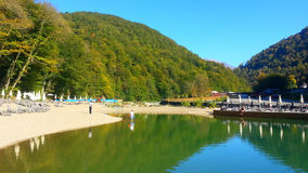 Beautiful autumn nature, lake in the mountains. Lake in the mountains, resort Krasnaya Polyana, Rosa Khutor, Sochi. Autumn nature at sunny day, water reflections Royalty Free Stock Photos
