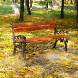Beautiful autumn park and benche. A beautiful bench for rest in an autumn park Stock Image