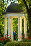 Beautiful autumn park composition with the girl in an arbor. Beautiful plot in autumn park with the girl in an arbor among white columns in the light of the Royalty Free Stock Photos