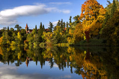 Beautiful autumn park , trees and Blue sky reflected in calm water. Stock Photos