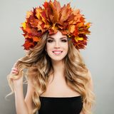 Beautiful autumn portrait of pretty cheerful woman in autumn leaves crown. Makeup, blonde curly hair.  stock image