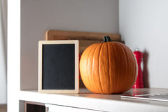 Beautiful Autumn pumpkin and blackboard menu. On a table in kitchen Stock Images