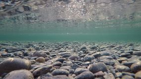 Beautiful autumn river bottom with ice flakes floating past and reflection on surface tension, underwater. 4k resolution video stock video