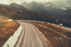 Highway in mountains turning to the tunnel. Beautiful autumn scenery with mountain road bending to the tunnel, hazy hill ridge in background, multiple pillars Royalty Free Stock Photography