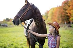Autumn season young girl and horse. In a beautiful Autumn season of a young girl and horse in a field Stock Photo