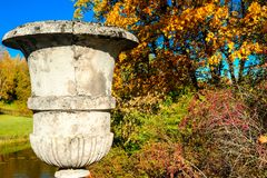 Beautiful autumn sunny landscape with old concrete vase on the bridge in the Pavlovsk park, red and orange leaves on royalty free stock image