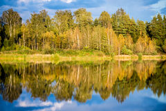 Beautiful autumn sunset at the lake with blue sky, red and orang Stock Photography