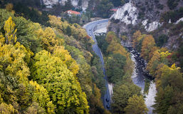 Beautiful autumn trees near a road and a river Stock Image