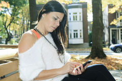 A beautiful autumn woman having good time. A beautiful autumn woman with cellphone on the hand Stock Images