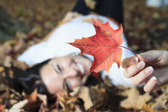 A beautiful autumn woman having good time. Lay on leafs show one of them Royalty Free Stock Photography