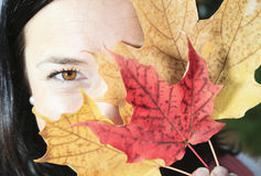 A beautiful autumn woman having good time. A beautiful autumn woman with leaf on face Stock Photos