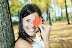A beautiful autumn woman having good time. A beautiful autumn woman with leaf in front of is eye Stock Image