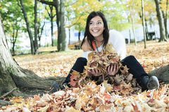 Beautiful autumn woman having good time. A beautiful autumn woman sitting on leafs Royalty Free Stock Photo