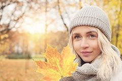 Beautiful autumn woman holding yellow maple leaf. Outdoors. Romantic girl on fall park background royalty free stock images