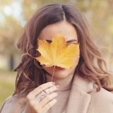 Beautiful autumn woman holding yellow maple leaf. Beautiful autumn woman with yellow maple leaf outdoors. Romantic girl in fall park royalty free stock image