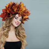 Beautiful autumn woman in autumn leaves crown on gray background.  stock image